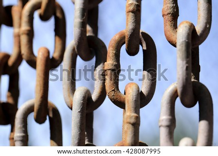Hanging rusty chain on blue sky background. - stock photo