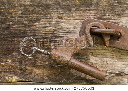 hanging rusty iron lock on a wooden door with dead bolt. open sticks in a castle key. hand made vintage - stock photo