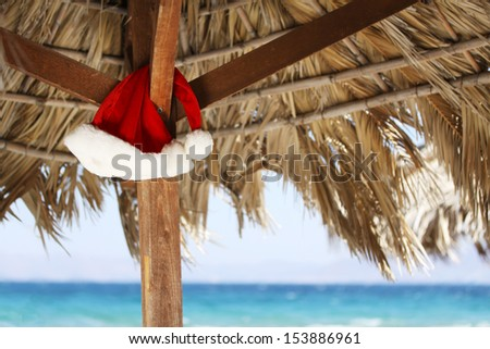 Hanging Santa Claus hat on palmy sunshade on beach - stock photo