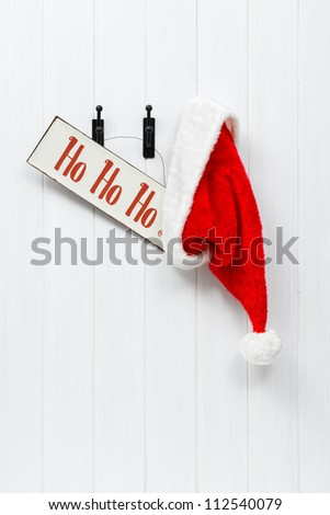 Hanging Santa Claus hat with hohoho sign - stock photo