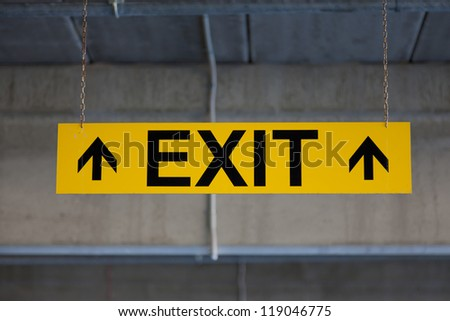 Hanging sign EXIT on yellow background - stock photo