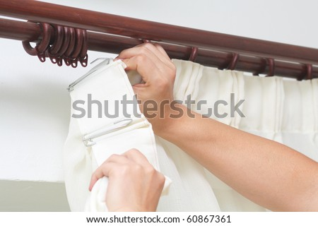Hanging up curtain using pleat hooks - stock photo