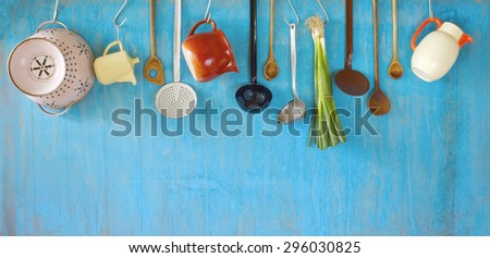 hanging vintage kitchen utensils and a bunch of green onions, cooking concept,copy space - stock photo