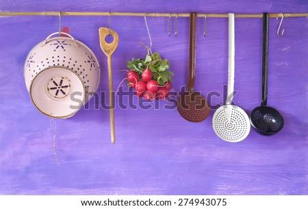 hanging vintage kitchen utensils and a bunch of radish, cooking concept,copy space - stock photo