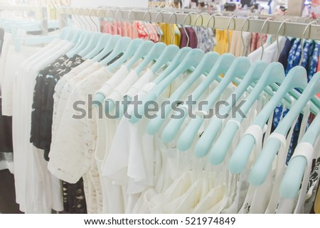 hanging white and black shirts on hanger in clothing store for sale : beauty and fashion and business concept