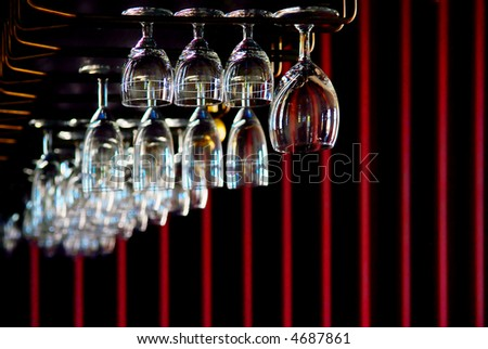 hanging wine and champagne glasses in a bar with dark background - stock photo
