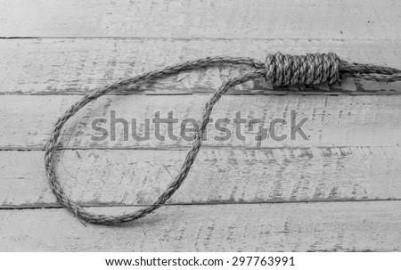 Hangman's noose on wooden table - stock photo