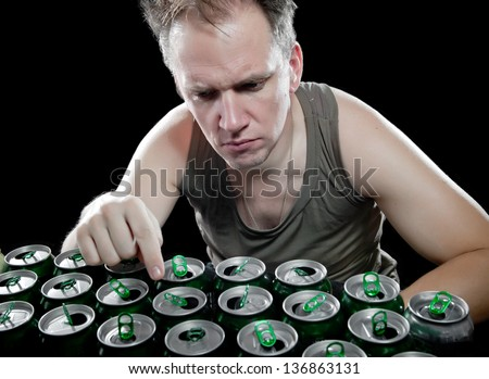 Hangover. The drunk man enumerates empty beer cans - stock photo