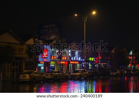 Hangzhou, China - December 3, 2014: Colorful Chinese neon advertising with reflections on wet road. Night street view