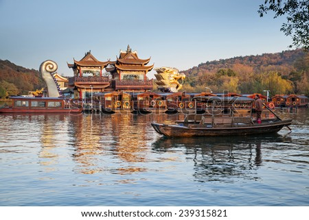 Hangzhou, China - December 5, 2014: Traditional Chinese wooden recreation boat with boatman floats on the West Lake. Famous park in Hangzhou city, China - stock photo