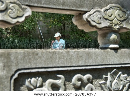 HANGZHOU, CHINA - MAY 4, 2015: Chinese worker resting at the Lingyin Temple, a Buddhist temple of the Chan sect located north-west of Hangzhou, Zhejiang Province, and important landmark. - stock photo