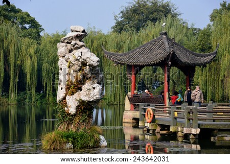 Hangzhou, China - November 17, 2014: Tourists take in the sights at West Lake in Hangzhou, which was made a UNESCO World Heritage Site in 2011. - stock photo