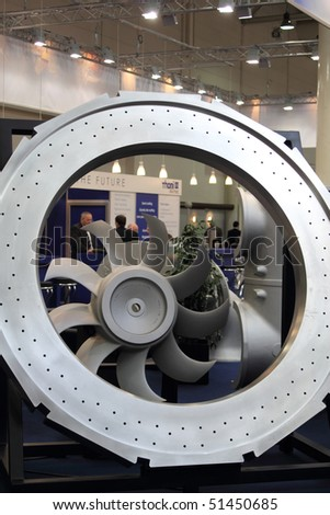HANNOVER, GERMANY - APRIL 19:big machine parts on a stand at the hannover industrial fair, business people in the background , Hannover Messe April 19, 2010 in Hannover, germany