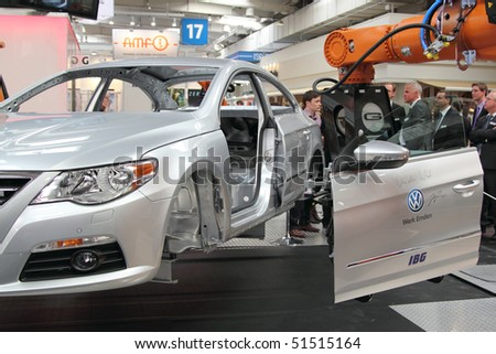 HANNOVER, GERMANY - APRIL 19: demonstration of an industrial handling robot fitting the doors to a car , Hannover Messe April 19, 2010 in Hannover, germany - stock photo