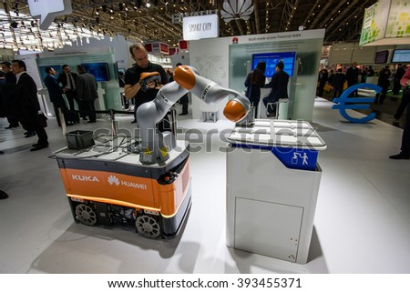 HANNOVER, GERMANY - MARCH 14, 2016: Industrial KUKA robot in booth of Huawei company at CeBIT information technology trade show in Hannover, Germany on March 14, 2016. - stock photo
