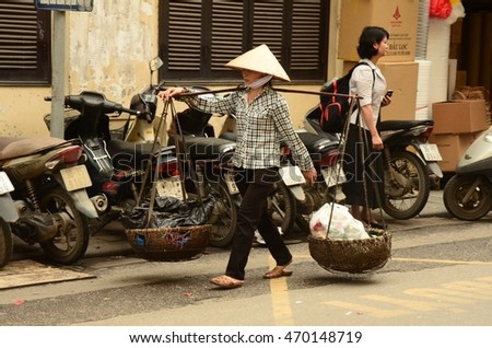 HANOI, VIETNAM - APRIL 4: a woman with a carrying pole on April 4, 2016 in Hanoi, Vietnam. A carrying pole is a yoke of wood or bamboo, used by people to carry a load.