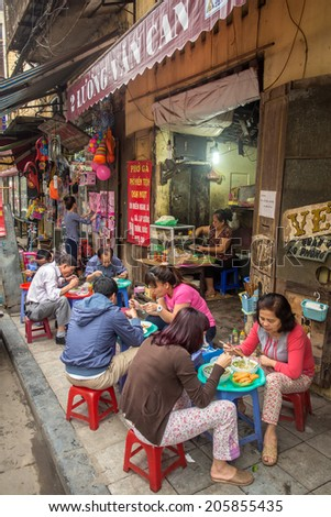 HANOI, VIETNAM - APRIL 8, 2014: Customers have their meal on the street stall on April 8, 2014 on Hanoi. Vietnamese people love to socialise as they eat. - stock photo
