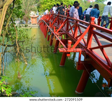 Hanoi, Vietnam - April 12, 2015: Tourists on the Red Bridge over Lake Hoan Kiem in central Hanoi, Vietnam. - stock photo