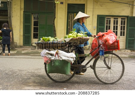 Hanoi, Vietnam - April 13, 2014: Unidentified food vendor sells fruits carried by bike on Hanoi street, Vietnam. The old looked house on background.