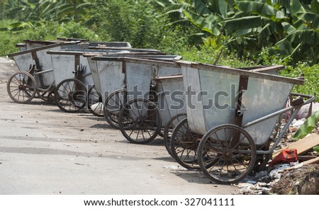 Hanoi, Vietnam - Aug 9, 2015: Dumpsters for collecting rubbish laying on a country road in a suburb area of Hanoi capital. - stock photo