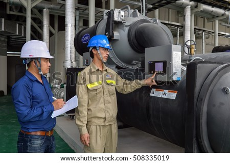 Hanoi, Vietnam 06 August 2016: Hawee worker operating Carrier Industrial Chillers, Cool water pump and pipe line for make reduce temperature condition in HVAC systems
