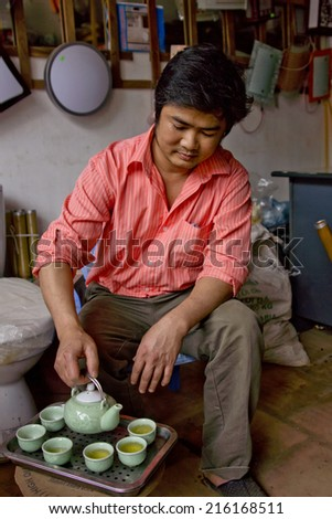 HANOI, VIETNAM - CIRCA MARCH 2012: Hardware store owner serving traditional tea to his customers as a welcome. Salmon colored shirt, green tea cups and a ceremonial gesture. - stock photo