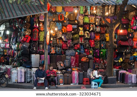 HANOI, VIETNAM, DECEMBER 16, 2014 : A couple is selling a very large choice of bags and suitcases in the streets of Hanoi, Vietnam - stock photo