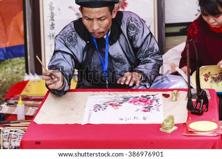 "HANOI, VIETNAM - FEB, 12: A scholar writes Chinese calligraphy characters at Temple of Literature on Feb 12,2016.""Calligraphy giving"" is a popular tradition during Tet holiday to Vietnamese people"
