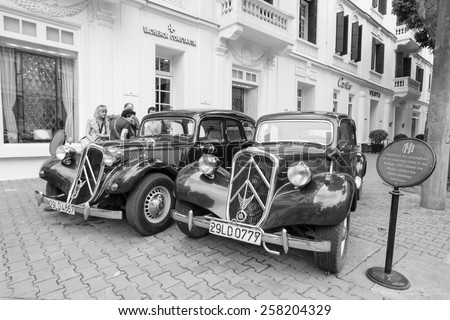 HANOI VIETNAM FEB 28 2015 Two old Citroen cars parking in front of Hotel Sofitel Legend Metropole Hanoi. These cars are for rent for tours around old street of Hanoi. - stock photo