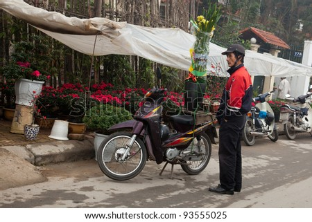HANOI, VIETNAM -  JAN 19: A motorcyclist stands at a flower stall purchasing yellow flowers for Tet (Lunar New Year) decoration in Hanoi, Vietnam, January 19, 2012