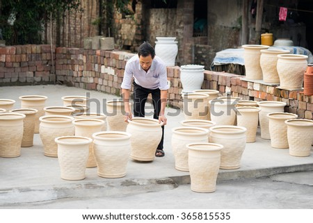 Hanoi, Vietnam - Jan 1, 2016: Asian crafsman processing ceramic brick after drying under the sunlight at Kim Lan traditional village, on the other river bank of Bat Trang village in Hanoi. - stock photo