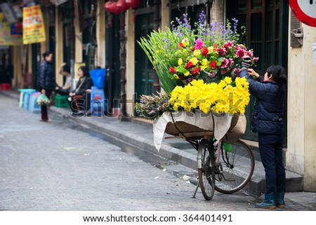 Hanoi, Vietnam - Jan 17, 206: Street vendors. They sell everything from flower, fruits, handicraft goods, bamboo and rattan goods to food.