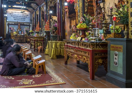 HANOI, VIETNAM - JANUARY 21, 2016: Women praying inside the ancient Tran Quoc Buddhist Pagoda in front of a richly ornamented shrine piled with offerings