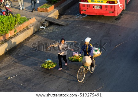 Hanoi, Vietnam - July 23, 2016: Aerial view of Vietnamese woman vendors carrying fruit on Yen Phu street in early morning