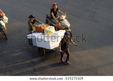 Hanoi, Vietnam - July 23, 2016: Aerial view of Vietnamese women transporting fruit by pull cart on Yen Phu street in early morning