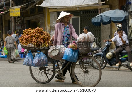 HANOI, VIETNAM - JUN 11: An unidentified Vietnamese woman is selling fruit from her bicycle on the streets of Hanoi.  Vietnam has one of the fastest growing economies in South East Asia.