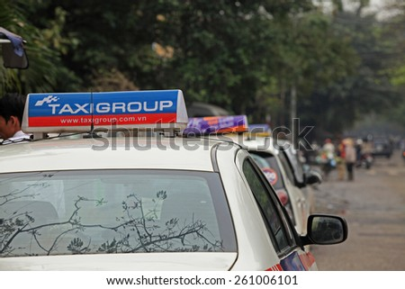 Hanoi, Vietnam - Mar 15, 2015: Taxi-cabs parking on the side of a street in Hanoi capital, Vietnam. Traffic is one of the most serious matter in the country with many vehicles on narrow streets.