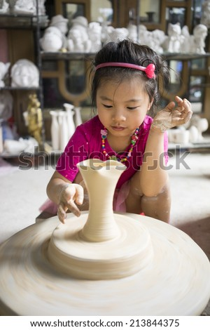 Hanoi, Vietnam - Mar 30, 2014: Unidentified little girl learn to form a lottery product in Bat Trang ancient pottery village, Hanoi, Vietnam  - stock photo