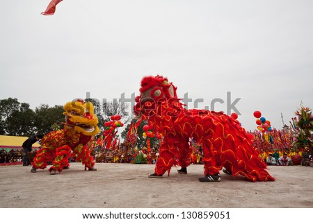 HANOI, VIETNAM - MARCH 24: A group of unidentified boys dance with their colorful lion during the Tet Lunar New Year celebrations on March 29, 2012 in Ha Noi City, Vietnam. - stock photo