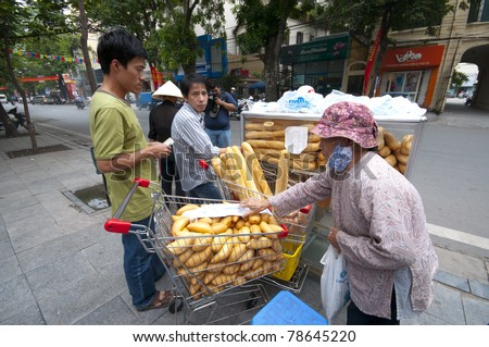 HANOI, VIETNAM - MAY 24: An unidentified road side baguette seller sells fresh baguettes in Hanoi on May 24, 2011. According to UNICEF, gross national income (GNI) for Vietnam in 2009 is USD$1,010.
