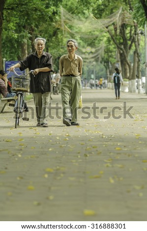 Hanoi, Vietnam, May 10, 2014: Two senior man walking around Hoankiem lake in Hanoi in the moring - a habit of the Hanoi people - stock photo