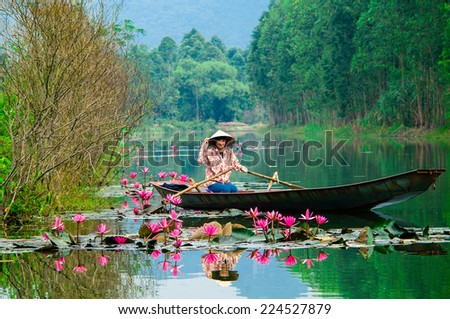 HANOI, VIETNAM - NOV 29: Girl in traditional costume rowing boat in the flooded forest in MYDUC, VIETNAM on November 29, 2013. MYDUC is a district about 60 km from Hanoi - stock photo