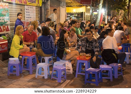 Hanoi, Vietnam - Nov 2, 2014: People drink beer on street at night in old quarter, center of Hanoi. Drinking beer on street is one of the most special culture of Hanoi. - stock photo