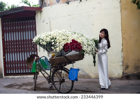 HANOI, VIETNAM - NOVEMBER 23: Vietnamese girl in traditional dress buying white daisy flower on street in Hanoi on November 23, 2014 in Hanoi, Vietnam. White daisy flowers bloom in November.