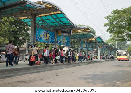 Hanoi, Vietnam - Oct 25, 2015: Line of people waiting for bus at bus station in Hanoi city - stock photo