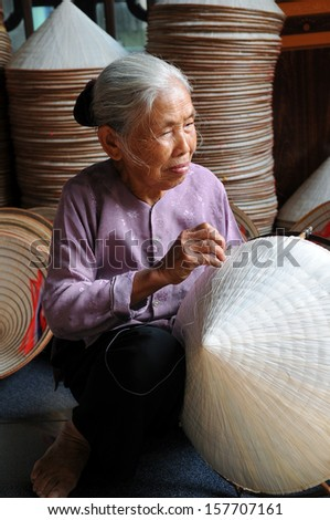HANOI, VIETNAM - OCTOBER 23: Vietnamese woman sitting sewing hats in a traditional village in Vietnam October 23, 2010. Conical hat is a traditional item of ethnic Vietnam - stock photo