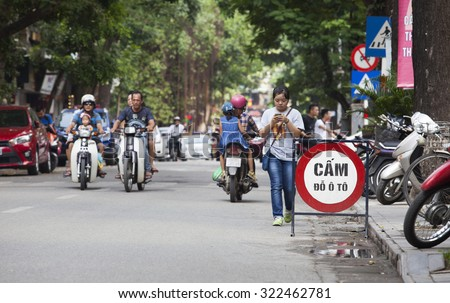 Hanoi, Vietnam - Sep 27, 2015: No parking sign standing on a street with some motorcycles traveling through in the old quarter street area of Hanoi capital.  - stock photo