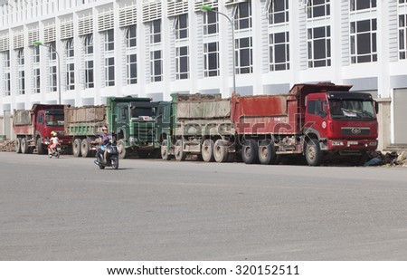 Hanoi, Vietnam - Sep 19, 2015: Trucks parking on the street side next to an under construction house complex in a suburb area of Hanoi capital.