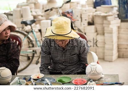 HANOI, VIETNAM - SEP 24, 2014: Unidentified Vietnamese man works at the ceramic workshop. Ceramic art is very popular in Asian culture - stock photo