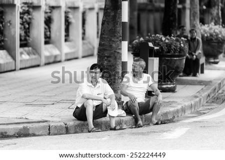 HANOI, VIETNAM - SEP 23, 2014: Unidentified Vietnamese men in the street. 92% of Vietnamese people belong to the Viet ethnic group - stock photo
